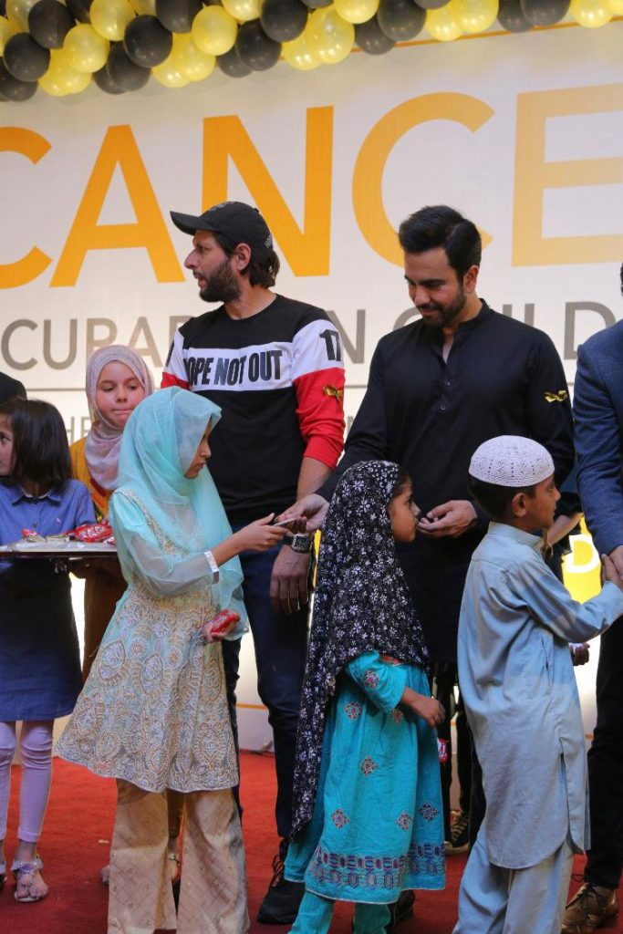junaid khan is distributing chocolates among children