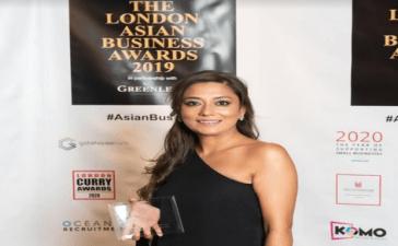 Aida Khan holding award